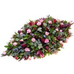 Rouwarrangement kistbedekkend in roze en rode tinten
